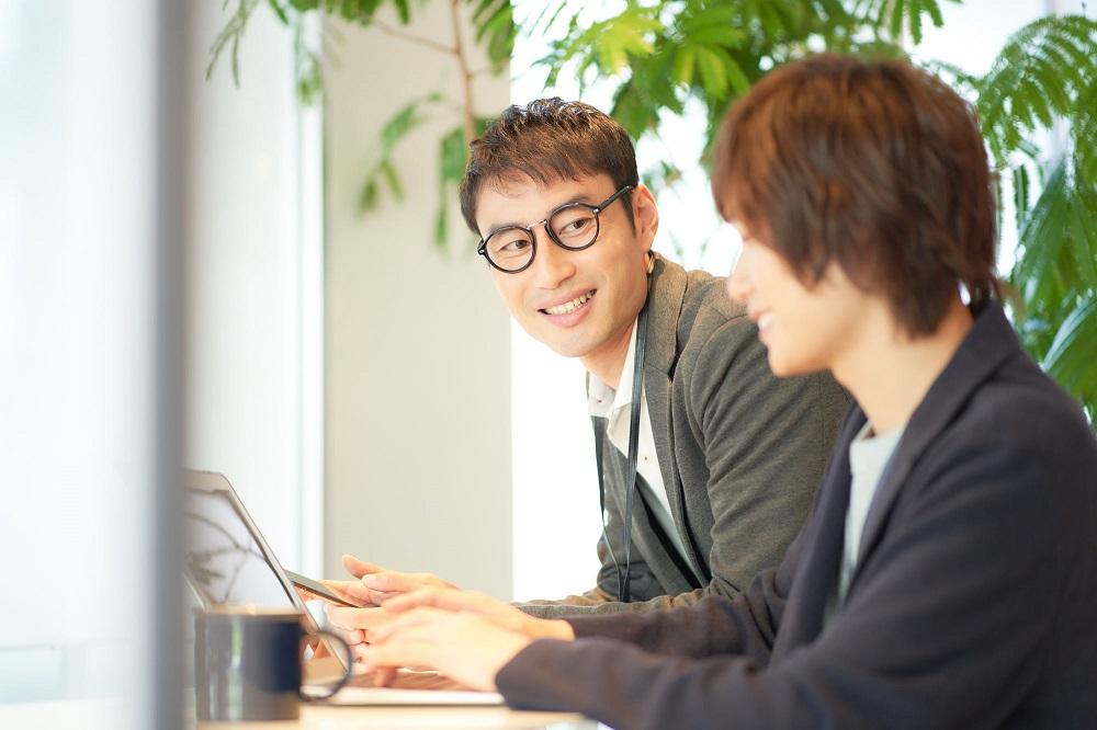 パソコンを操作する2人の男性